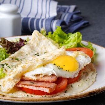 目玉焼き、ベーコン、トマトのオムレツ。朝の朝食のコンセプト