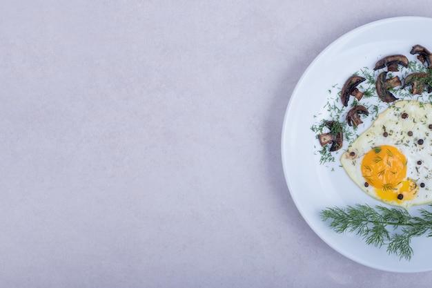 白い皿にキノコを揚げたオムレツ。