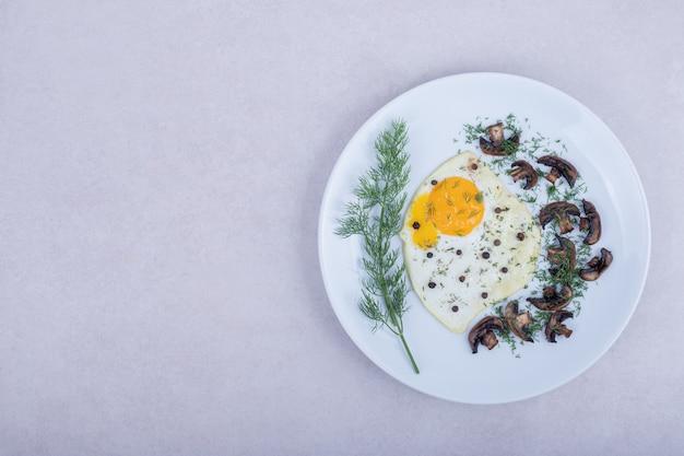 Омлет с жареными грибами на белой тарелке.