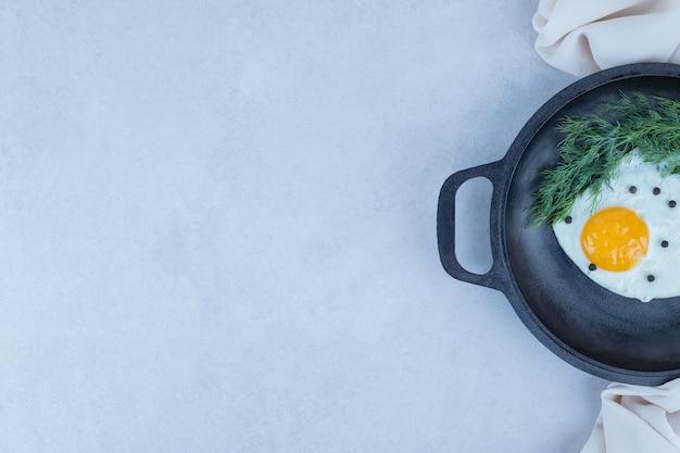 白の暗い鍋にコショウとオムレツ