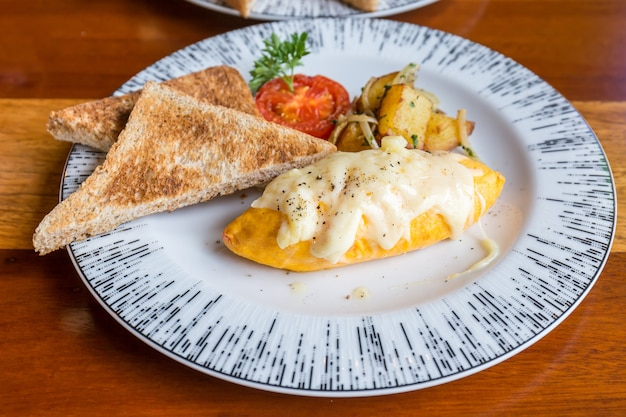 Omelet with potato, tomatoes parsley and feta cheese and bread in white plate on wooden