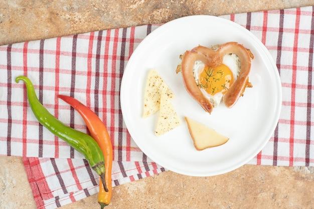 Омлет с колбасой в белой тарелке на скатерти