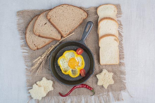 荒布の上に茶色のパンのスライスとオムレツ。