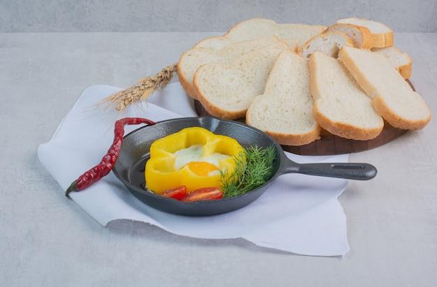 Омлет с кусочками белого хлеба на белой скатерти.
