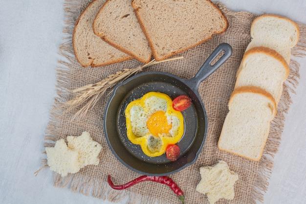 Frittata con fette di pane bianco su tela di sacco.