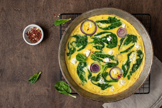Omelet with spinach and feta cheese in an iron pan on a wooden, rustic . top view. copyspace
