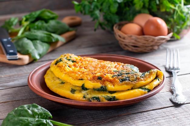 Омлет с листьями шпината. омлет на тарелке, яичница