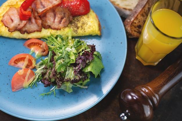 토마토, 버섯, 베이컨 오믈렛. 어두운 표면에서 아침 식사