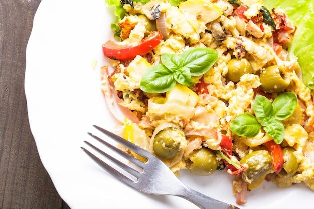 Омлет с овощами и беконом на тарелке