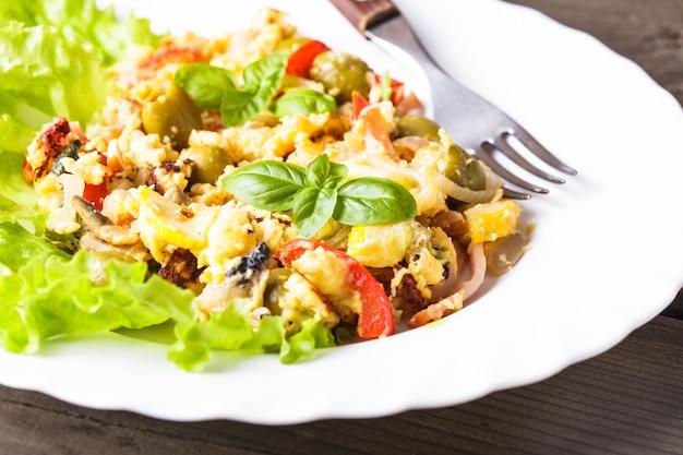 皿に野菜とベーコンのオムレツ Premium写真