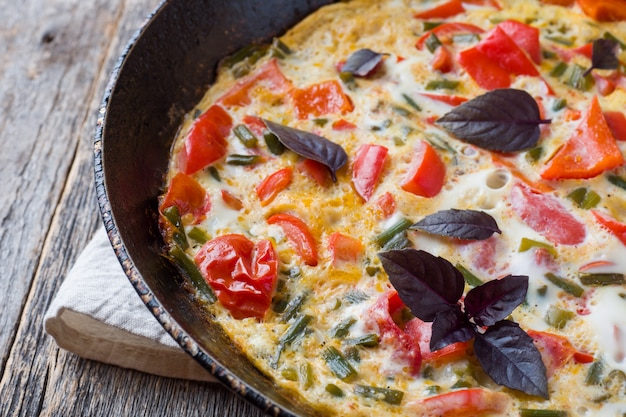 Omelet with vegetables in a pan close-up.