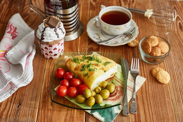 Omelette, cake, biscuits, tomatoes, olives on the table