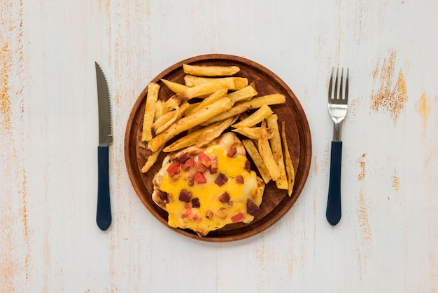 Omelette and french fries on wooden board on grunge painted desk