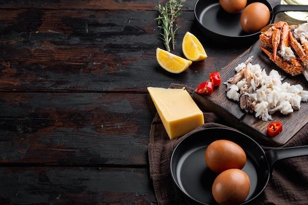 Ингредиенты омлета с перцем, крабовым мясом, яйцом, сыром, на темном деревянном фоне, с copyspace и местом для текста