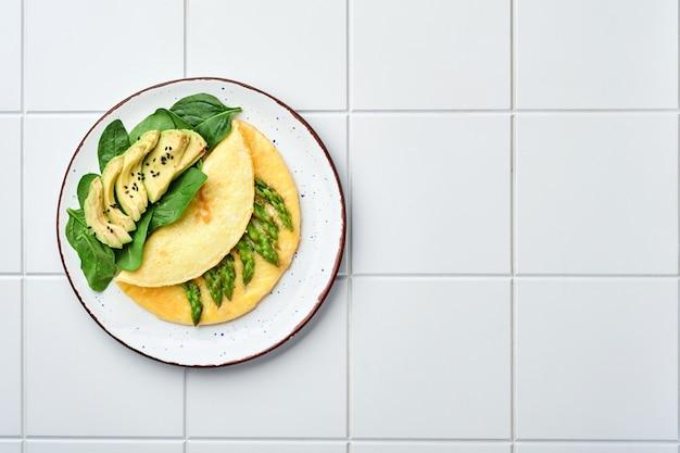 오믈렛 또는 아스파라거스, 아보카도 및 시금치 잎을 타일 표면에 얹습니다. 평면도.