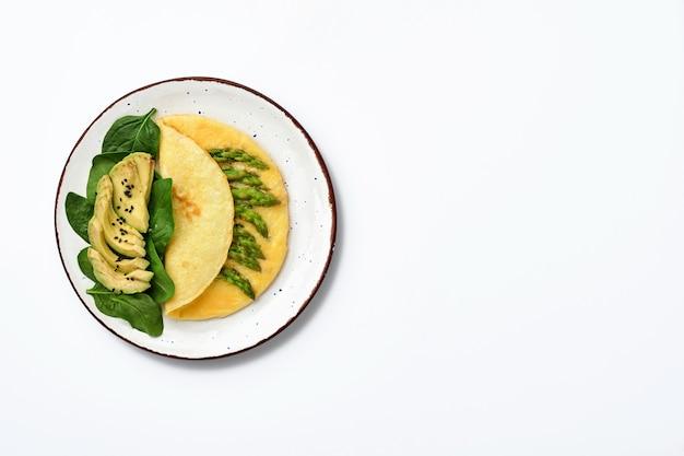 오믈렛 또는 흰색 표면에 아스파라거스, 아보카도 및 시금치 잎. 평면도.