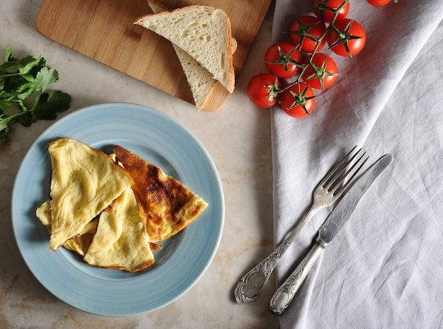 Omelette on a plate, parsley, tomatoes, toast