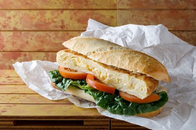 Сэндвич с омлетом с листьями салата и помидорами