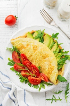 Omelette with avocado, tomatoes and arugula on white ceramic plate on light stone surface. healthy breakfast. selective focus. top view.