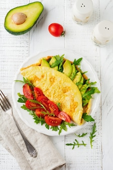 Omelette with avocado, tomatoes and arugula on white ceramic plate on light stone surface. healthy breakfast