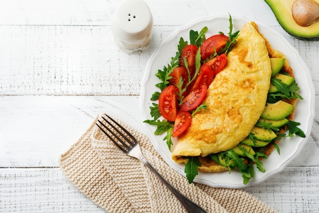 Omelette with avocado, tomatoes and arugula on white ceramic plate on light stone surface