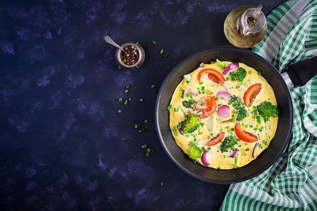 Омлет с брокколи, помидорами и красным луком в сковороде. итальянская фриттата с овощами. вид сверху, сверху