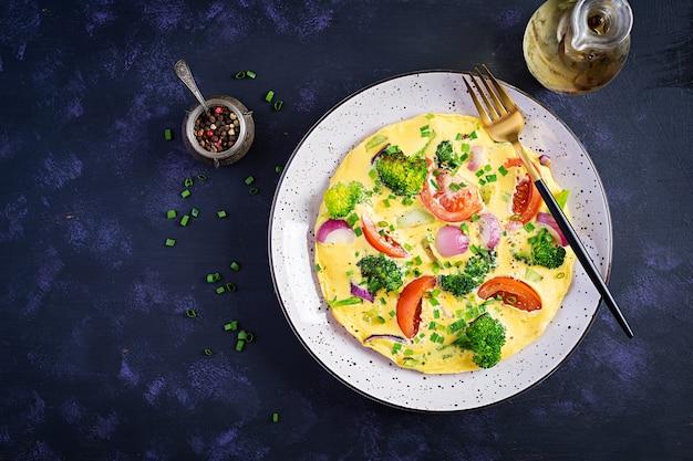 Омлет с брокколи, помидорами и красным луком на темном столе. итальянская фриттата с овощами. вид сверху, сверху