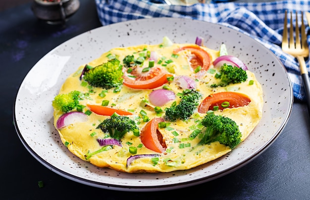 Omelette with broccoli,  tomatoes and red onions on dark table. italian frittata with vegetables.