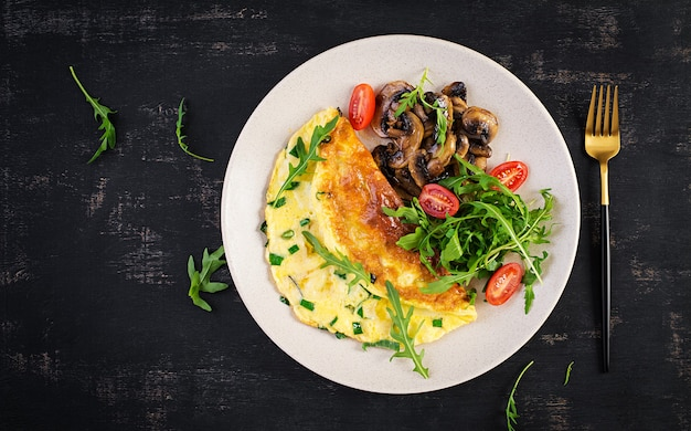 Omelette with cheese, green herbs and fried mushrooms on plate.  frittata - italian omelet. top view, above, copy space