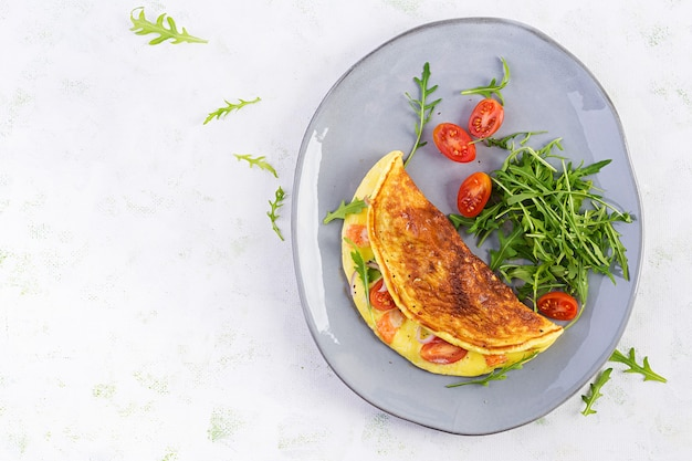 Omelette with cheese, tomatoes and avocado on light table. italian frittata
