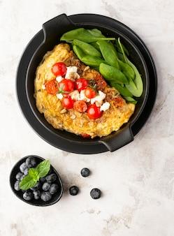 Frittata con formaggio e pomodori sulla piastra