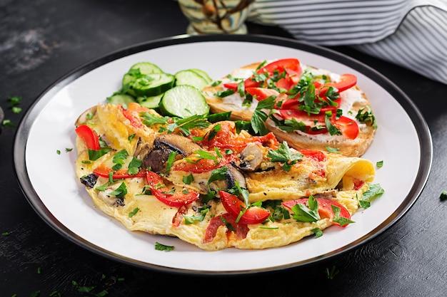 Омлет с грибами, болгарским перцем, помидорами и бутербродом со сливочным сыром на белой тарелке. фриттата - итальянский омлет.