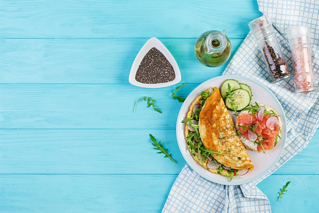 Omelette with radish, green arugula and sandwich with salmon on white plate