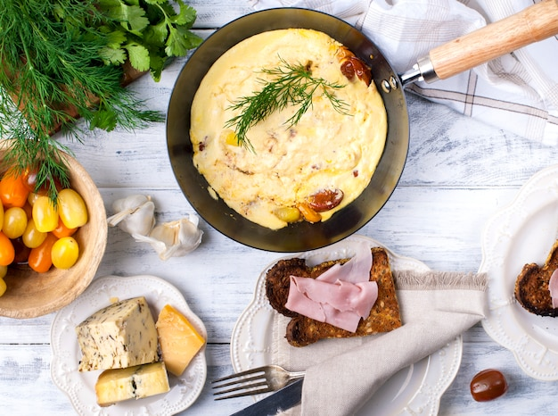 Omelette with tomato in a frying pan for breakfast, cheese and greens on a white wooden background