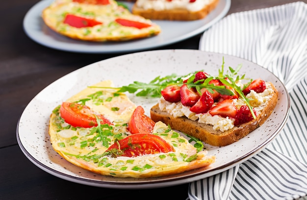 Omelette with tomatoes, ham and green onion on dark table