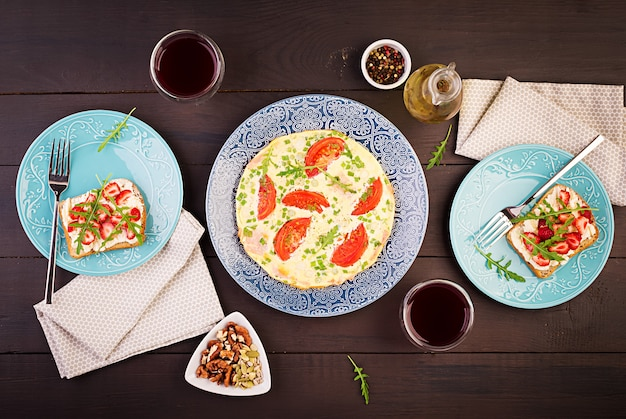 Omelette with tomatoes, ham, green onion and sandwich with strawberry on dark table, top view
