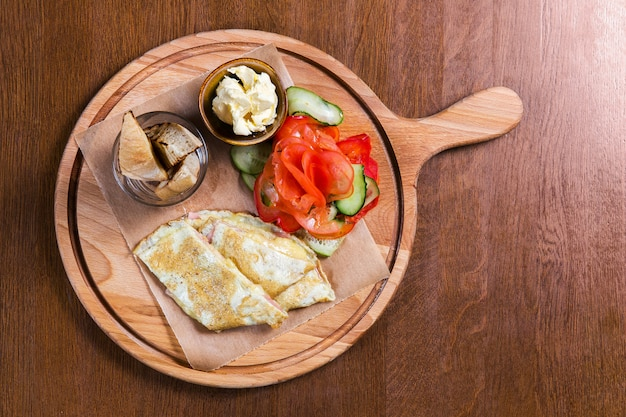 Omelette with vegetables and bread on wooden table in the restaurant. tasty food. gourmet