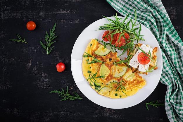 Омлет с кабачками, зеленью и бутербродом с сыром фета на тарелке. фриттата - итальянский омлет. вид сверху, сверху, копировать пространство