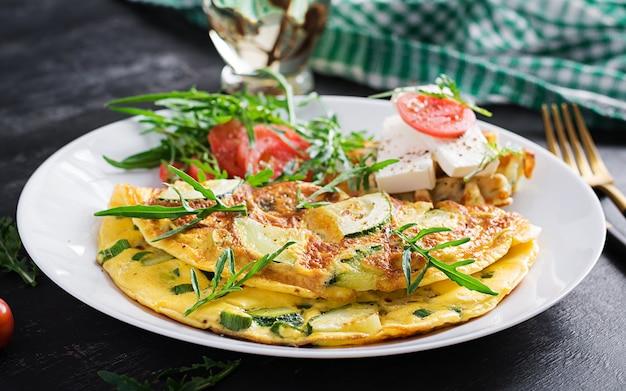 Омлет с кабачками, зеленью и бутербродом с сыром фета на тарелке. фриттата - итальянский омлет.