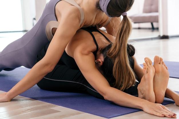 Примета делает растяжку на коврике в классе йоги, лежа друг на друге