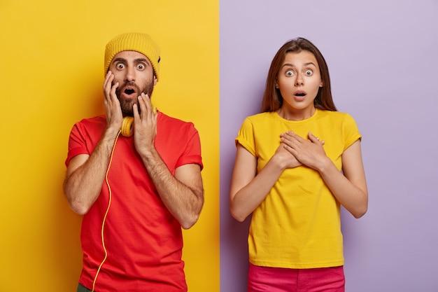 Omgのコンセプト。愚かな若い女性と男性は、恐怖から言葉を失い、息を切らし、顔の表情に衝撃を与えました