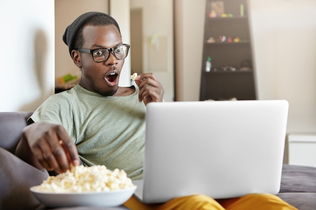 Omg. excited emotional young dark-skinned man in hat and rectangular glasses sitting on couch at home with laptop computer and bowl of popcorn, watching detective series online with mouth wide open