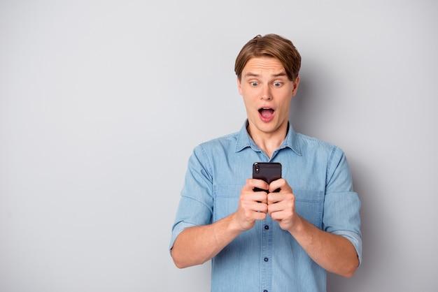 Омг последователи! удивленный парень использует свой смартфон, читает новости социальных сетей, кричит, вау, невероятно носить модную одежду, изолированную на сером цветном фоне