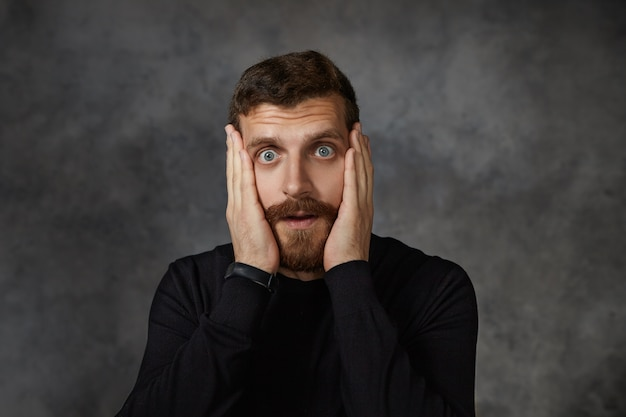 Omg. frustrated shocked amazed young bearded guy with trimmed mustache keeping hands on his face and  with eyes popped out, reacting emotionally on unexpected astonishing news