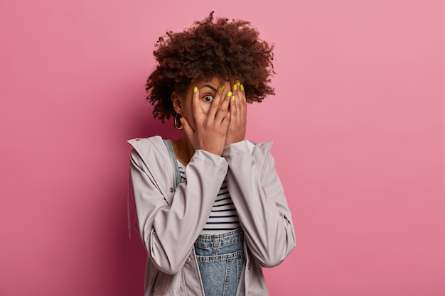 Omg, how scarying! frightened curly haired woman peeks through fingers, hides face with palms, looks with scared expression, doesnt want to see something awful, wears grey jacket isolated on pink wall