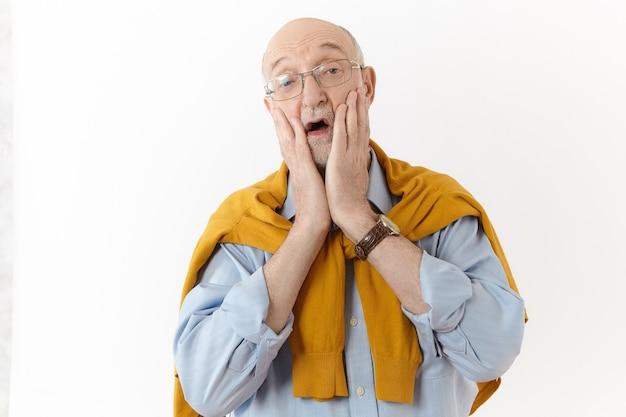 ああ、神様。人間の感情と反応。眼鏡をかけたスタイリッシュでエレガントな成熟した引退した男性が頬に手をつないで、口を大きく開けて叫び、予期せぬニュースにショックを受けた写真