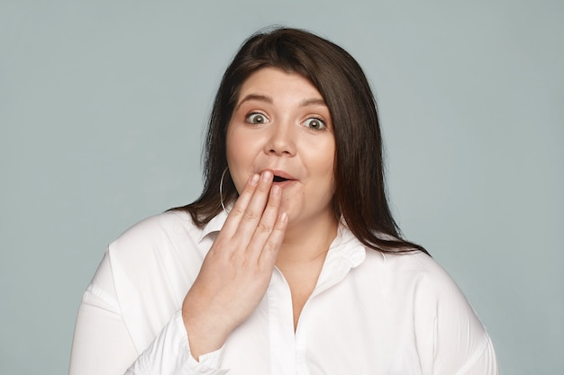 Omg. human reaction and emotions. portrait of astonished fascinated young obese caucasian woman employee with chubby cheeks covering mouth, shocked with unexpected gossip about her colleague