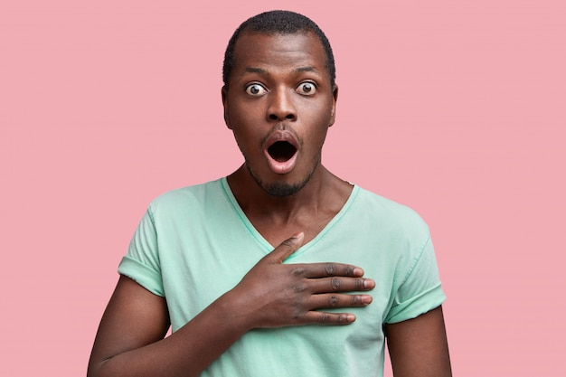 Omg, i can`t beleive my eyes! shocked amazed dark skinned young male stares at camera with eyes popped out and opened mouth