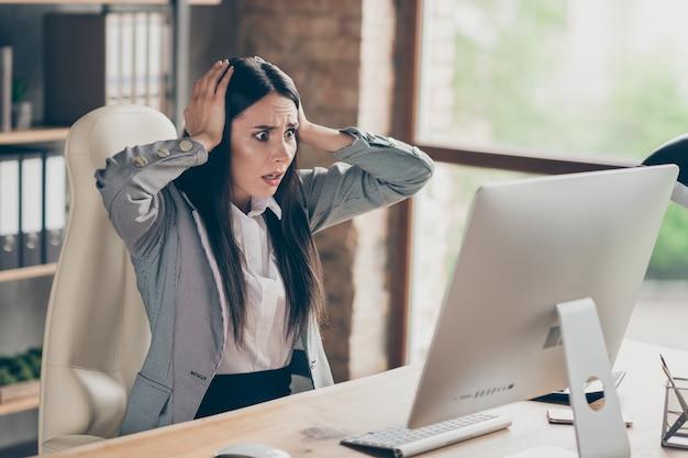 Омг, я выстрелил. паника разочарованная девушка воротник инвестор сидеть за столом работа удаленный компьютер компьютер сенсорные руки голова впечатлен социальная сеть уведомление о потере работы носить блейзер на рабочем месте рабочая станция