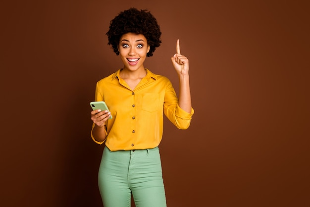 Omg i know what text! excited crazy afro american girl blogger use smartphone type sms think get incredible idea raise finger up wear yellow stylish green outfit isolated brown color